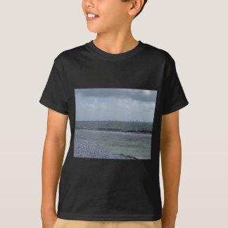 Seashore of beach with sailboats on the horizon T-Shirt