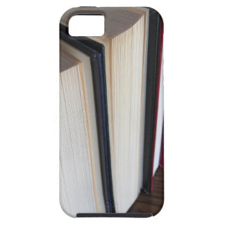 Second hand books standing on a wooden table case for the iPhone 5