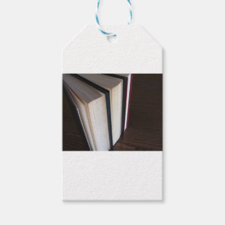 Second hand books standing on a wooden table gift tags