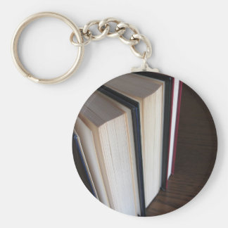 Second hand books standing on a wooden table keychain