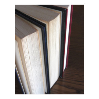 Second hand books standing on a wooden table letterhead