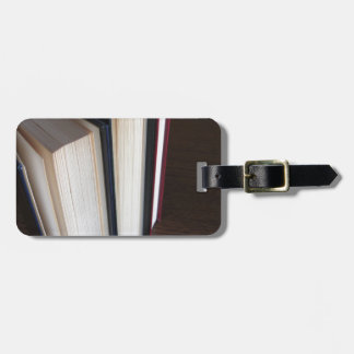 Second hand books standing on a wooden table luggage tag