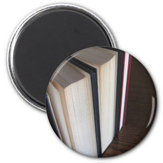 Second hand books standing on a wooden table magnet