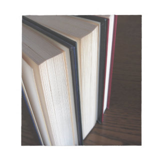 Second hand books standing on a wooden table notepad