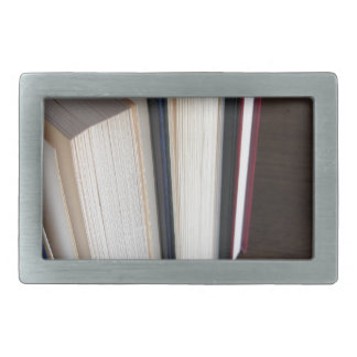 Second hand books standing on a wooden table rectangular belt buckles