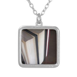 Second hand books standing on a wooden table silver plated necklace