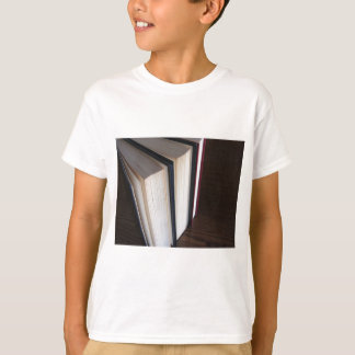 Second hand books standing on a wooden table T-Shirt