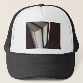 Second hand books standing on a wooden table trucker hat