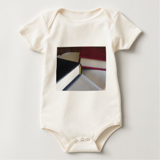 Second hand books with blank pages on a table baby bodysuit