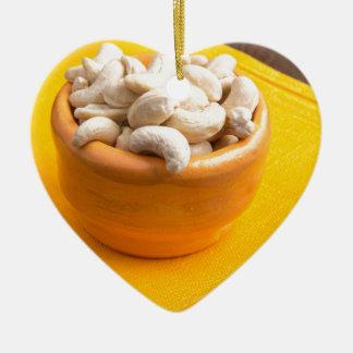 Selective focus on raw cashew nuts closeup ceramic heart ornament