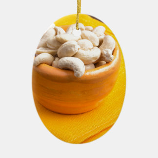 Selective focus on raw cashew nuts closeup ceramic oval ornament