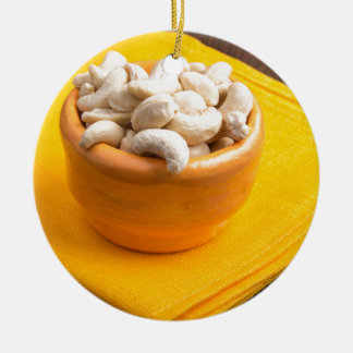 Selective focus on raw cashew nuts closeup round ceramic ornament