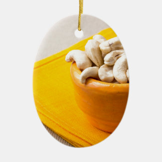 Selective focus on raw cashew nuts in a small cup ceramic oval ornament