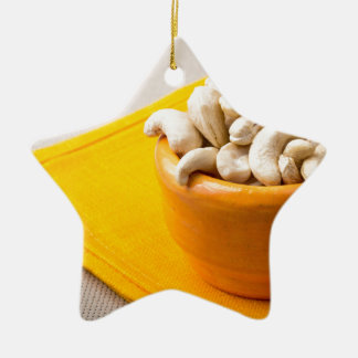 Selective focus on raw cashew nuts in a small cup ceramic star ornament