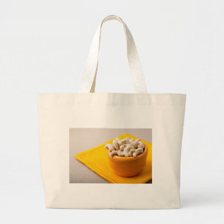 Selective focus on raw cashew nuts in a small cup large tote bag