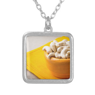 Selective focus on raw cashew nuts in a small cup silver plated necklace