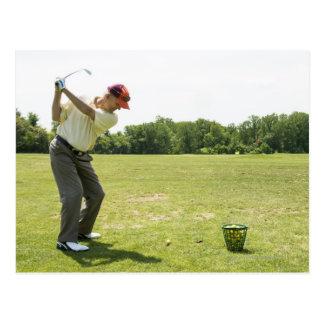 Senior golfer hitting practice balls at a range postcard