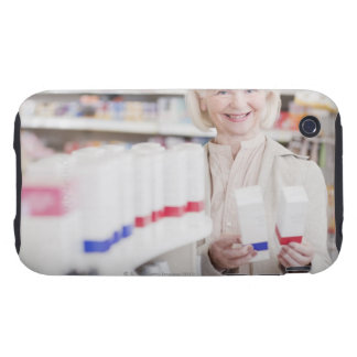 Senior woman comparing packages in drug store tough iPhone 3 covers