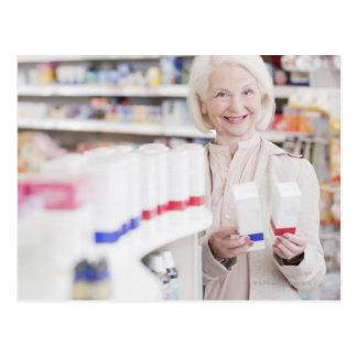 Senior woman comparing packages in drug store postcard
