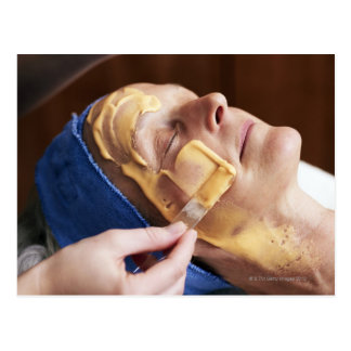 Senior woman having facial cream applied postcard