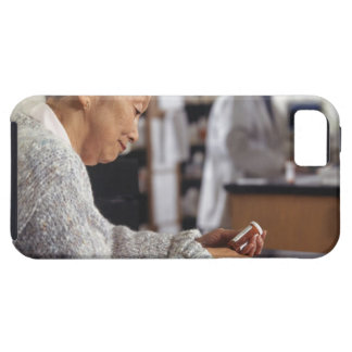 Senior woman in pharmacy reading medicine bottle iPhone 5 cases