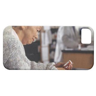 Senior woman in pharmacy reading medicine bottle iPhone 5 case