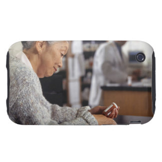 Senior woman in pharmacy reading medicine bottle iPhone 3 tough cover