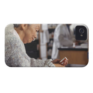 Senior woman in pharmacy reading medicine bottle iPhone 4 Case-Mate cases