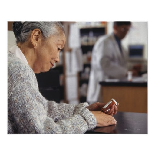 Senior woman in pharmacy reading medicine bottle posters