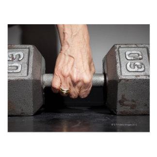Senior woman lifting weights postcards