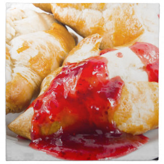 Several croissants with strawberry jam napkin