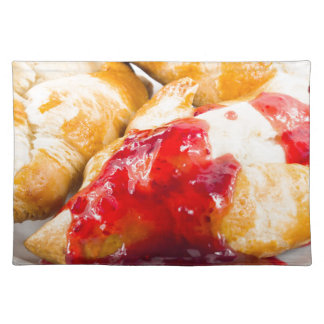 Several croissants with strawberry jam placemat