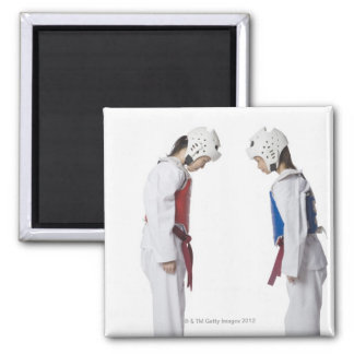 Side profile of two taekwondo players bowing square magnet