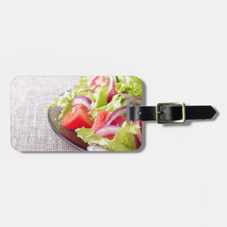 Side view of a plate of fresh salad closeup luggage tag