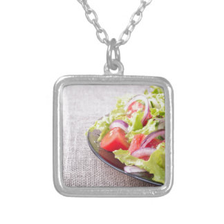 Side view of a plate of fresh salad closeup silver plated necklace