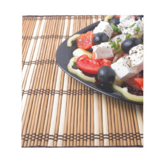Side view of fresh vegetarian salad on plate notepad