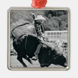 Side view of rider hanging on to bucking bull metal ornament