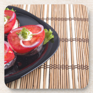 Side view of the cut slices of red tomatoes coaster