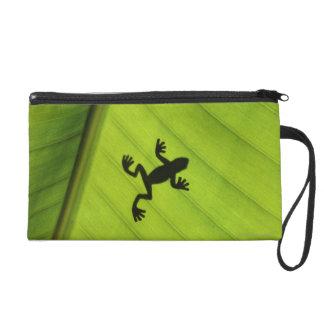 Silhouette of frog through banana leaf wristlet clutch