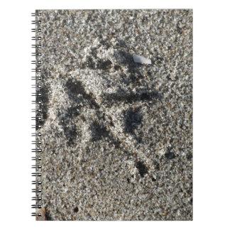 Single footprint of seagull bird on beach sand notebook