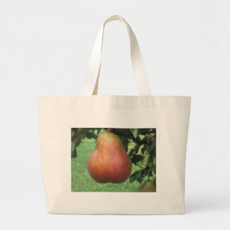 Single red pear hanging on the tree large tote bag