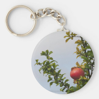Single red pomegranate fruit on the tree in leaves keychain