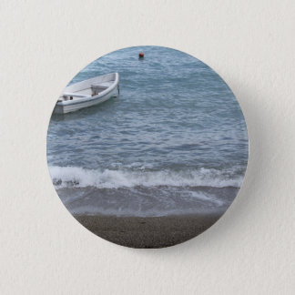 Single rowing boat moored in a harbor on the sea 2 inch round button