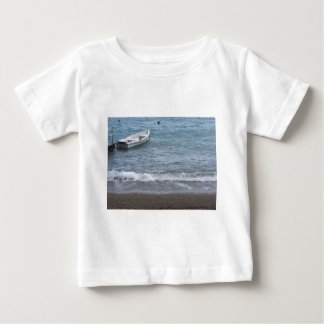 Single rowing boat moored in a harbor on the sea baby T-Shirt