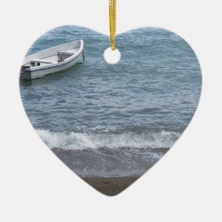 Single rowing boat moored in a harbor on the sea ceramic ornament