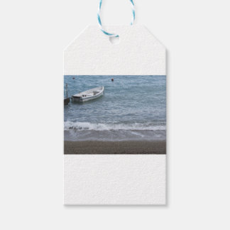 Single rowing boat moored in a harbor on the sea gift tags