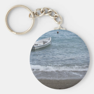 Single rowing boat moored in a harbor on the sea keychain
