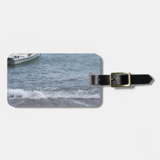 Single rowing boat moored in a harbor on the sea luggage tag