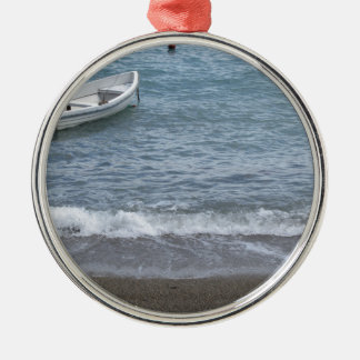 Single rowing boat moored in a harbor on the sea metal ornament
