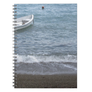 Single rowing boat moored in a harbor on the sea notebooks